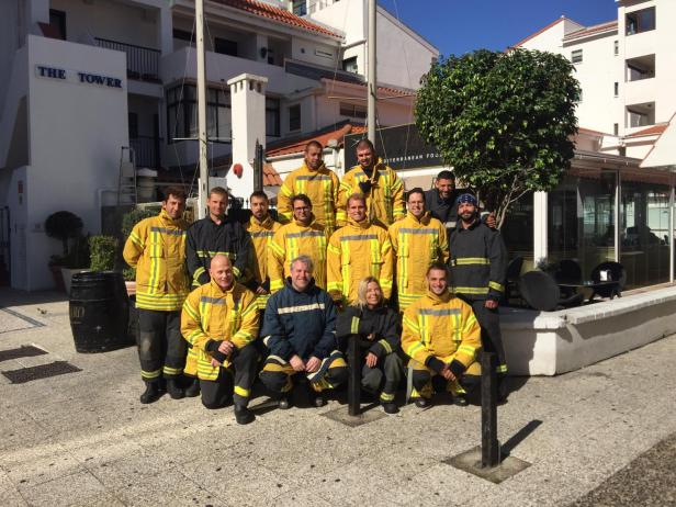 STCW class posed for a group photo in firefighting gear